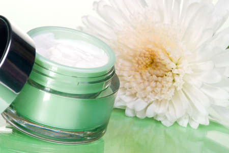 moisten: Closeup of container of moisturizing face cream and white chrysanthemum on green toned background