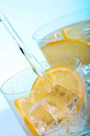 Pouring fresh water into one of two glasses with cocktails, sliced lemon and ice cubes over aqua paper background