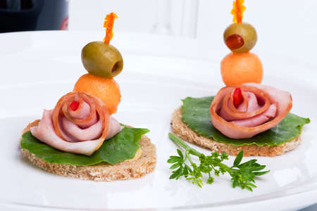 Closeup of two delicious ham and melon canapes-sandwiches made from ham, melon green salad and olive with red wine bottle in background photo