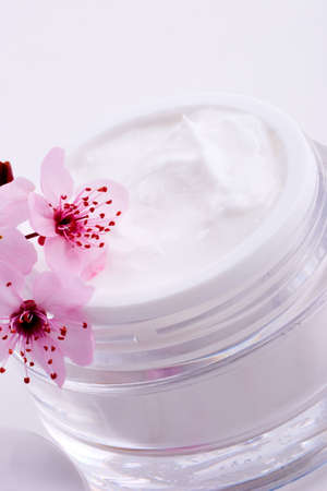 Extreme closeup of open container of moisturizing face cream and blooming twig of plum Stock Photo - 957620