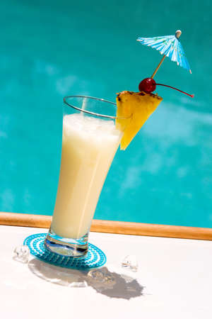 Glass of Pina Colada cocktail on swimming pool side