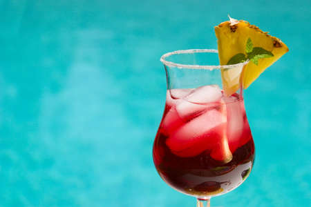 Glass of cranberry alcohol cocktail on swimming pool side Stok Fotoğraf