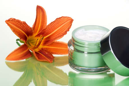 Closeup of container of opened moisturizing face cream and blooming lily on green toned background Stock Photo