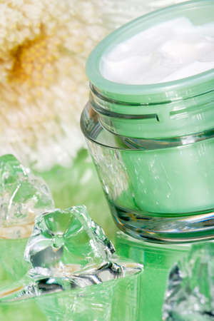moisten: Closeup of container of moisturizing face cream and white chrysanthemum on green toned surface arounded by melted ice cubes