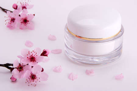 Closeup of container of moisturizing face cream and blooming twigs of plum with small pink petals around Stock Photo - 1050521