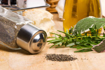 Pepper pot with black pepper, garlic, slice of fresh bread, bottle of olive oil and spicy herbs on wooden cut board photo