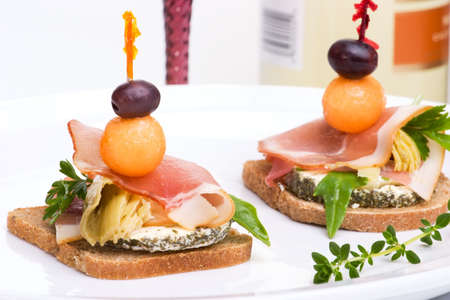 Closeup of two delicious Prosciutto canapes-sandwiches made from marinated artichoke, goat cheese,  Prosciutto ham, melon and olive over white background photo