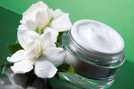 Closeup of container of opened moisturizing face cream and blooming fragrant white gardenias over green toned background