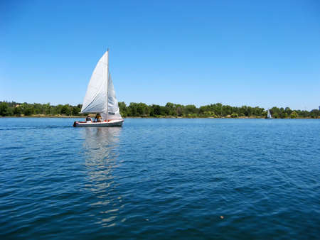 yacht race: Sailboat sailing on early morning blue water river
