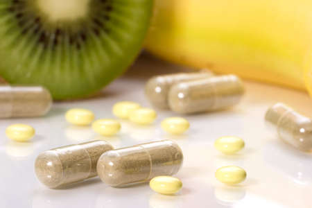 Closeup of medial pills in focus and fruits in background out of focus. Shallow DOF. Image suited for health topics about choice between medicine and healthy food