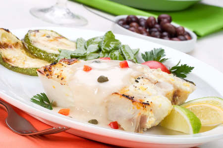 capers: Grilled halibut with capers and pepper sauce served with grilled zucchini, lemon, lime, tomatos and green peas Stock Photo