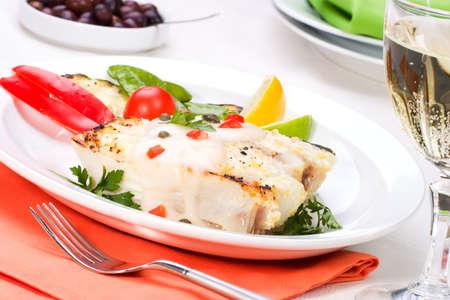 alcaparras: Flet�n asado con alcaparras y pimienta servido con salsa de calabac�n asado, lim�n, lima, tomate. guisantes verdes y vaso de vino blanco  Foto de archivo