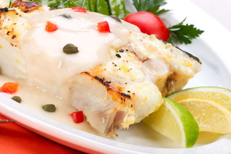 c�pres: Le fl�tan grill� avec les c�pres et la sauce � poivre a servi avec le citron, la chaux, les tomates et les pois