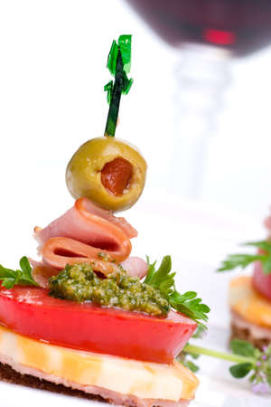 toothpick: Closeup of delicious Pesto cheese and ham canape-sandwich made from Pesto, cheese, ham, tomato and olive served with red wine in background