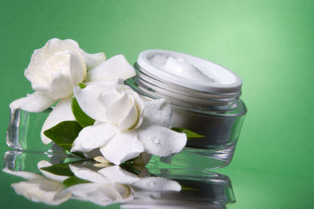 Closeup of container of opened moisturizing face cream and blooming fragrant white gardenias on melted icecubes over green toned background Stock Photo - 1457172