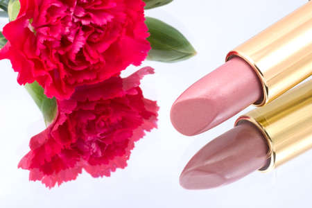 Closeup of lipstick with beautiful scarlet carnation on reflected mirror  Reklamní fotografie