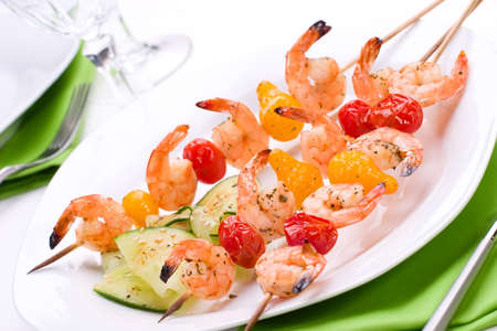 Grilled shrimps and pear tomatoes on bamboo sticks served with cucumber sesame salad in dinner setting photo