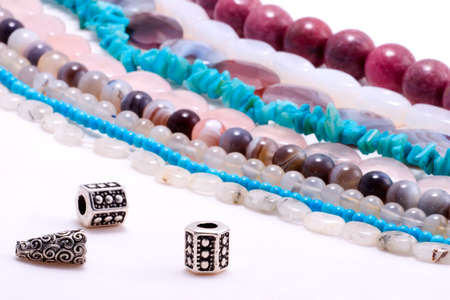 gem stones: Assorted strings of gem stones beds and spacer beads in front Stock Photo