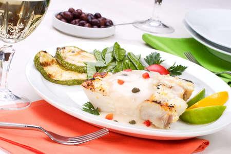 alcaparras: Flet�n asado con alcaparras y pimienta servido con salsa de calabaza asada, lim�n, lima, tomate. guisantes y vaso de vino blanco