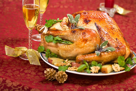 garnished: Garnished turkey on Christmas decorated table with candle and flutes of champagne Stock Photo