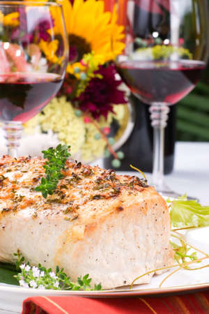 arrangment: Delicious garlic thyme roast pork loin is ready for dinner in middle of fall arrangment table and two glasses of red wine.