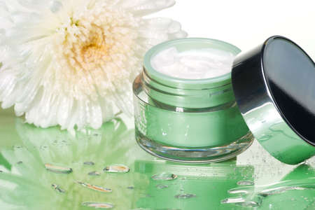 Closeup of container of moisturizing face cream and white chrysanthemum on green toned background Stock Photo - 1806919