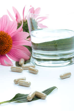 echinacea: Closeup of Echinacea extract pills, fresh Echinacea flowers and glass of water best suited for alternative medicine ads. Shallow DOF.