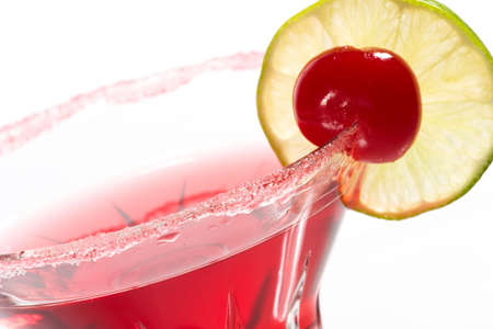 Closeup of Cosmopolitan cocktail in martini glass. Vodka, cranberry juice, triple sec liqueur, lime juice, garnished with lime and maraschino cherry. Most popular cocktails series. photo