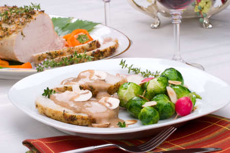 redwine: Delicious sliced garlic thyme roast pork loin with mushrooms sauce, brussels sprouts, almonds and radish ready for dinner in middle of fall arrangment table and two glasses of red wine.