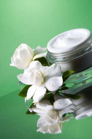 cremas faciales: Closeup de contenedor abierto de cara crema hidratante y blanco que florece fragantes gardenias icecubes derretido en m�s de tono verde de fondo