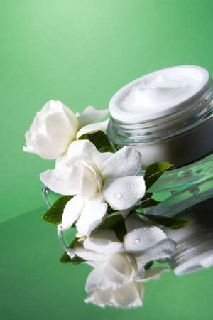 Closeup of container of opened moisturizing face cream and blooming fragrant white gardenias on melted icecubes over green toned background
