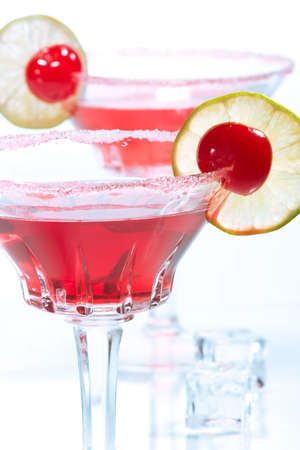Closeup of two Cosmopolitan cocktails in martini glasses. Vodka, cranberry juice, triple sec liqueur, lime juice, garnished with lime and maraschino cherry. Most popular cocktails series. photo