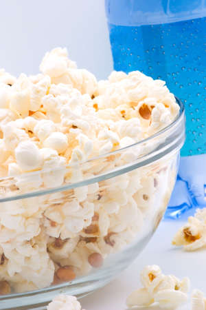 Closeup of glass bowl of popcorn and bottle of sparkling water in background photo