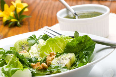 Sharp and sweet green organic salad with walnut and lime-pepper dressing for dinner photo
