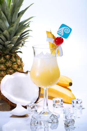 Pina Colada cocktails surrounded by tropical fruits. Rum, pineapple juice, coconut cream  garnished with slice of pineapple, coconut and maraschino cherry. Most popular cocktails series. photo