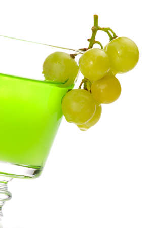 Closeup of glass of green colored liquor and bunch of grapes dipped into it over white background