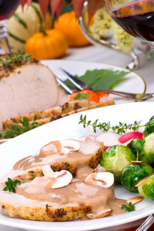Delicious sliced garlic thyme roast pork loin with mushrooms sauce, brussels sprouts, almonds and radish ready for dinner in middle of fall arrangment table and two glasses of red wine. Stock Photo - 2047594