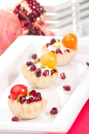 Three mini fillo shells filled with cream cheese, Pomegranates, cherry tomatoes and pistachio nuts on holiday table