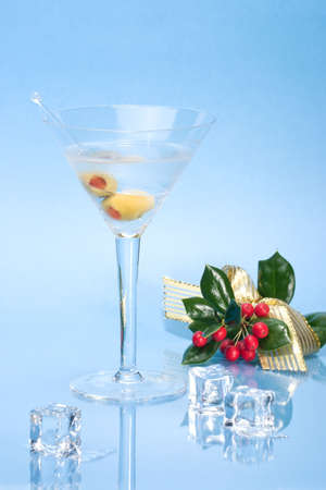 Closeup of martini in glass and Christmas decoration with ice cubes over aqua background on reflection surface photo