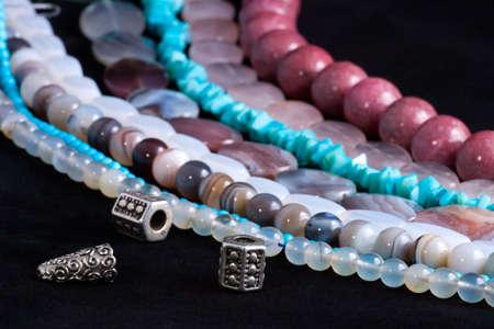 gem stones: Assorted strings of gem stones beds over black background Stock Photo