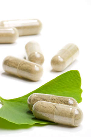 extract: Closeup of Ginkgo Biloba extract pills and fresh Ginkgo Biloba leaves best suited for aged people alternative medicine ads