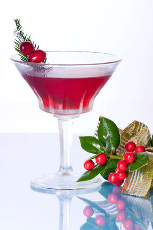 Closeup of Cosmopolitan cocktail in martini glass and Christmas decoration