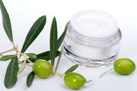 Closeup of jar of moisturizing face cream and twig with green olives.