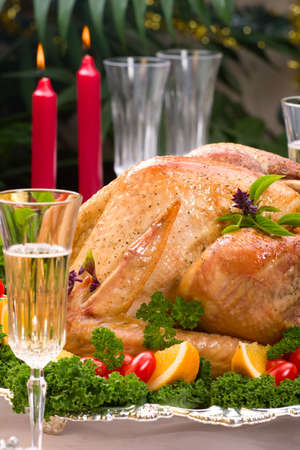 veggie tray: Closeup of garnished roasted turkey on Christmas decorated table with candles and flutes of champagne. Shallow dof. Stock Photo