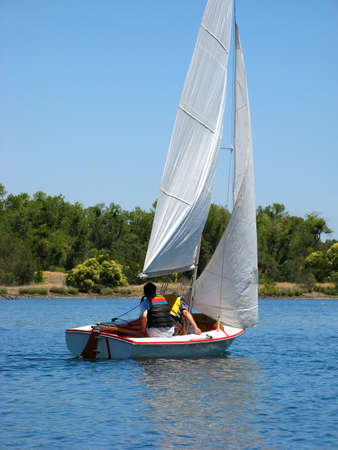 Sailboat sailing on early morning blue water river