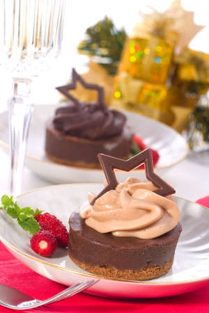 Couple of delicious chocolate cheesecake served with fresh strawberries and mint. Flute of champagne. Christmas ornament out of focus in background photo