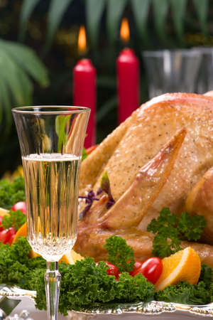 garnished: Garnished roasted turkey on Christmas decorated table with candles and flutes of champagne. Shallow DOF. Focus on glass.