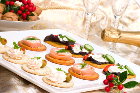 Tray with fresh sandwiches on holiday table with Christmas decoration, glasses and bottle of champagne photo