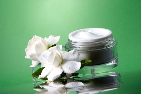 moisten: Closeup of container of opened moisturizing face cream and blooming fragrant white gardenias on melted icecubes over green toned background