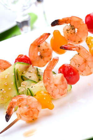 Closeup of grilled shrimps and pear tomatos on bamboo sticks served with cucumber sesame sald in dinner setting. Shallow DOF, focus on first row. photo